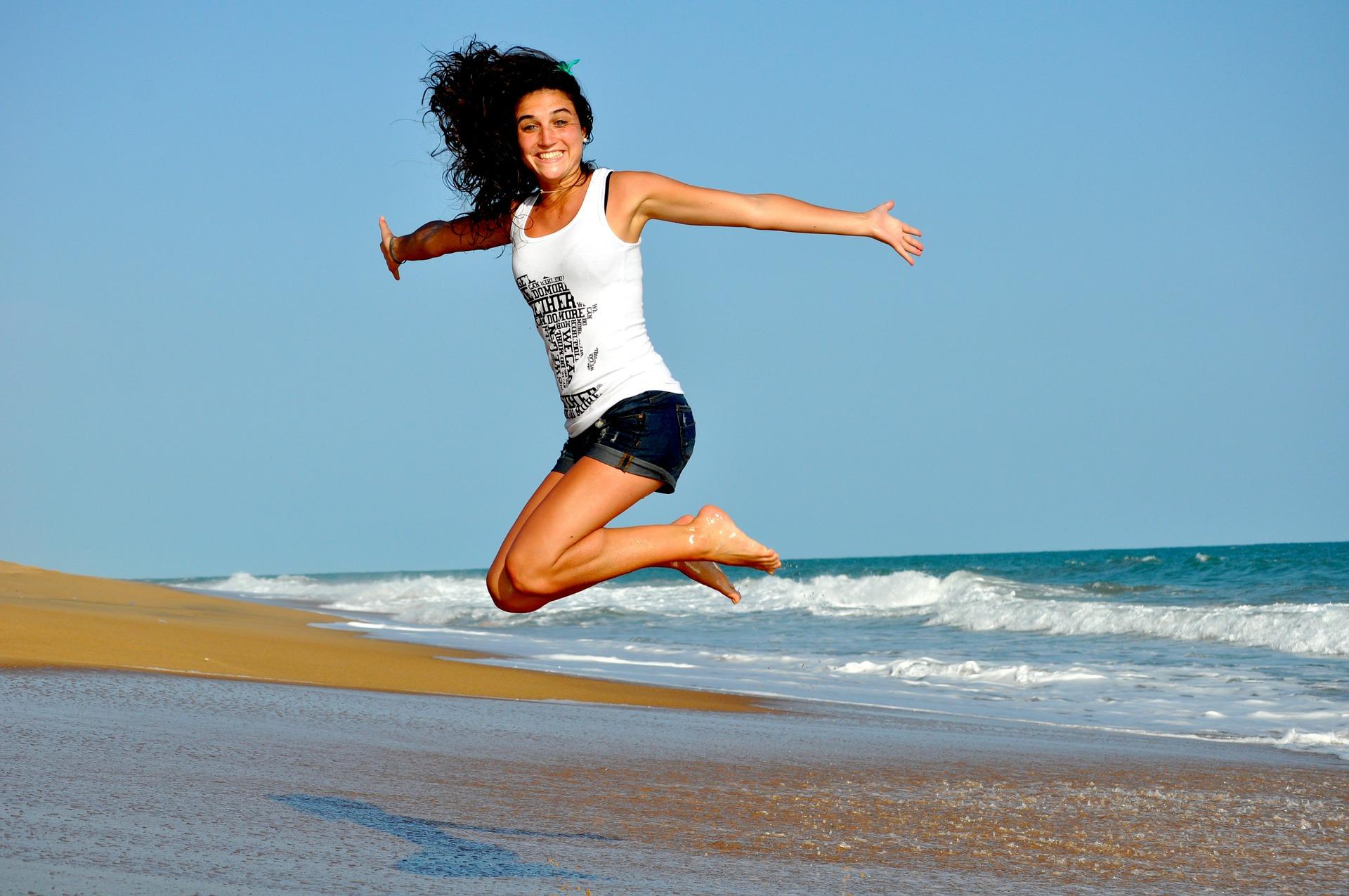 Glad kvinde hopper på strand