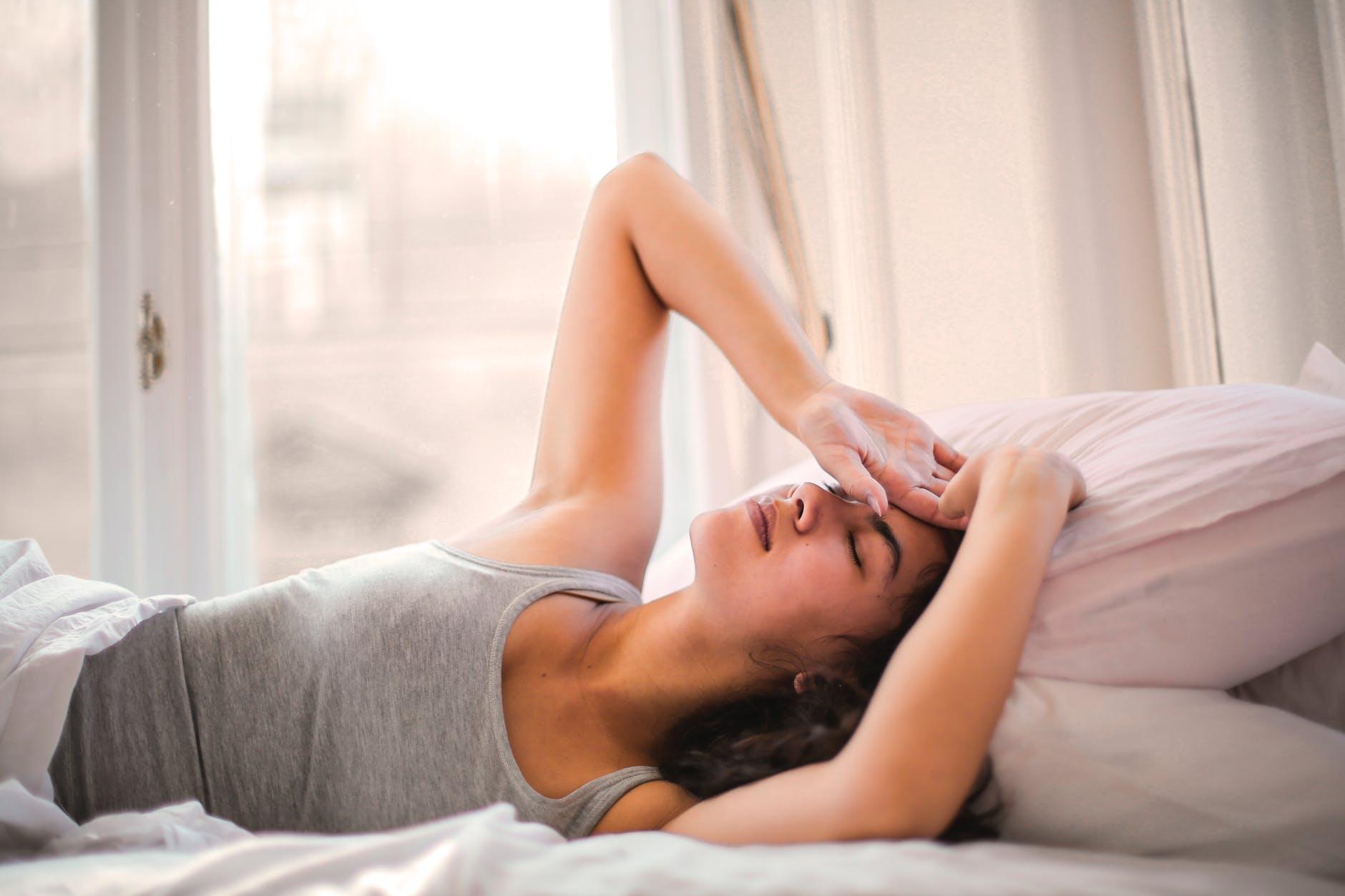 Kvinde med lukkede øjne i seng