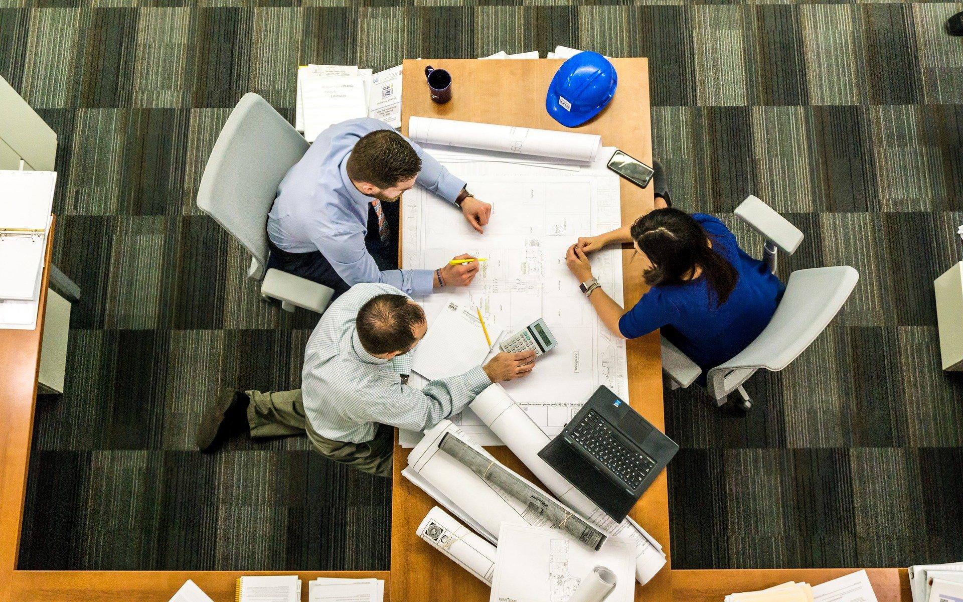 personer holder møde ved et skrivebord